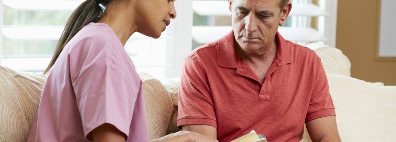 Pflegerin spricht mit Patienten im Wohnzimmer