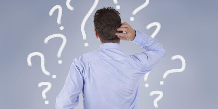 Mann schaut auf Wand voller Fragezeichen