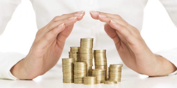 Hände über gestapelte Münzen