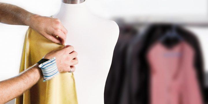 Designer steckt ein Kleidungsstück auf Puppe