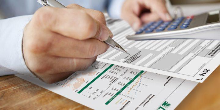 Mann berechnet seine LV 1871 Finanzen mit einem Taschenrechner