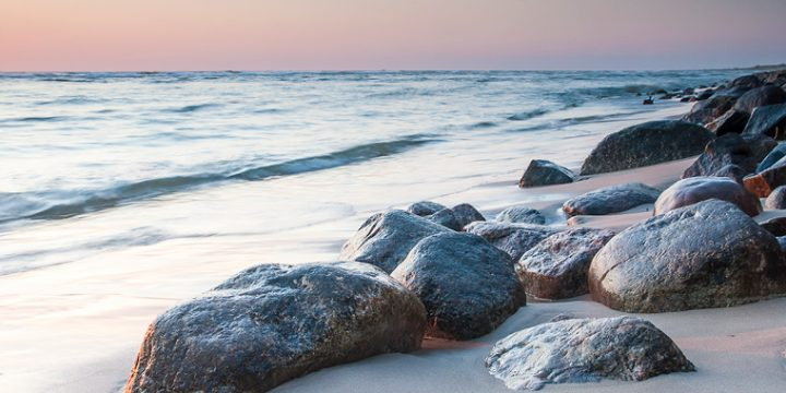 Strand mit Steinen im Sand