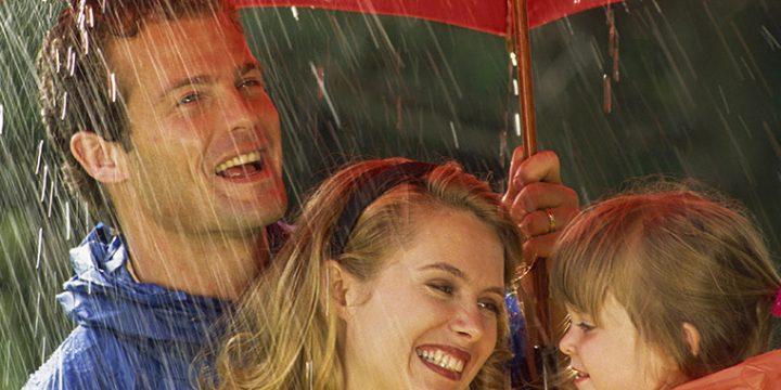 Familie teilt sich bei Regen ein Regenschirm