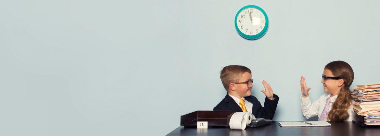 Schüler sitzen am Schreibtisch und klatschen sich ab