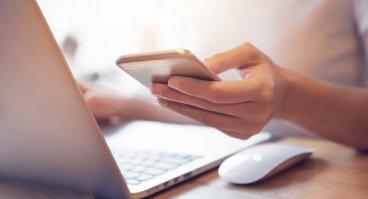 Bild der Hand einer Frau die am Laptop sitzt am Smartphone tippt