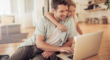 Vater und Tochter schauen auf ein Laptop