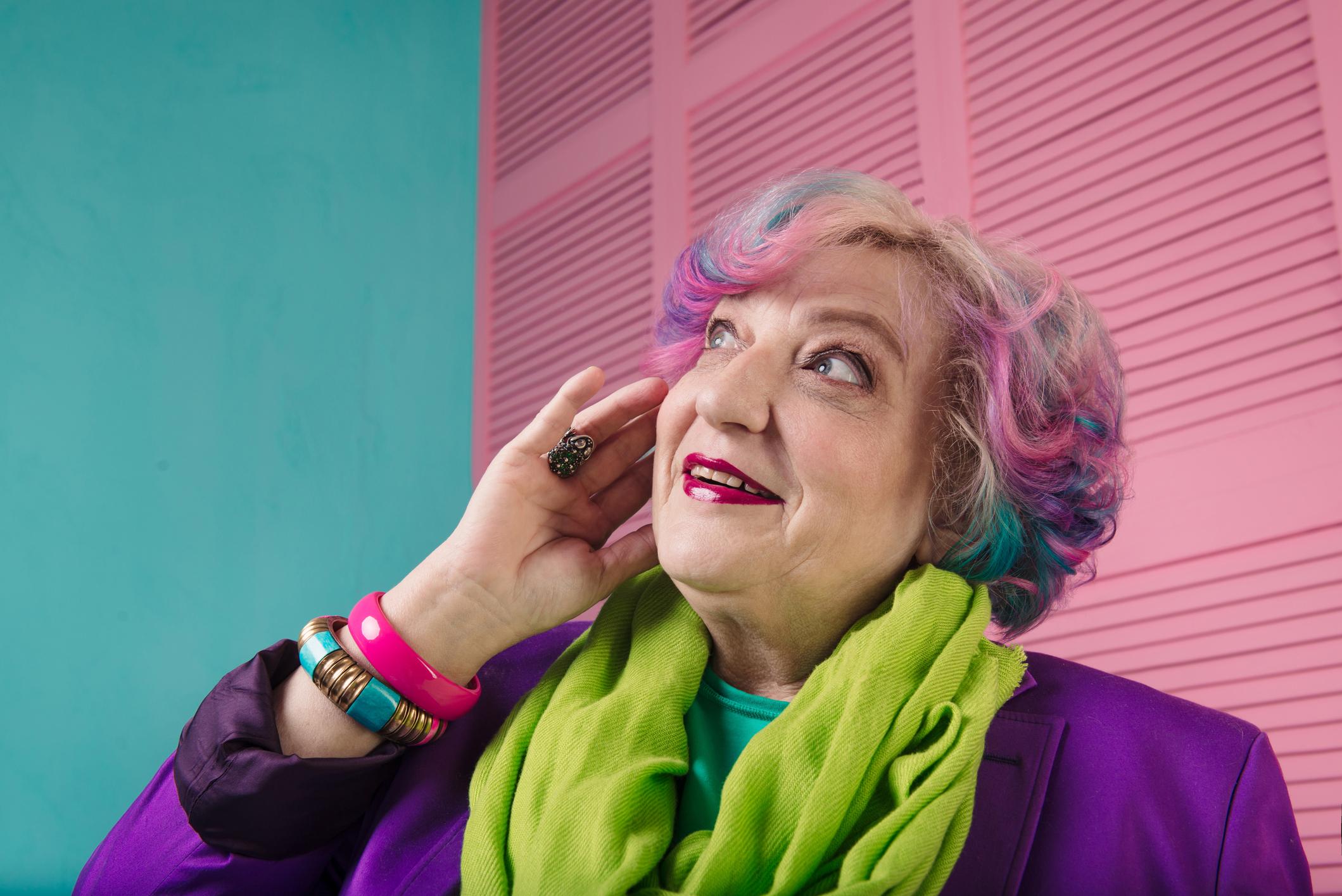 Überraschte stylishe Rentnerin sieht nach oben.