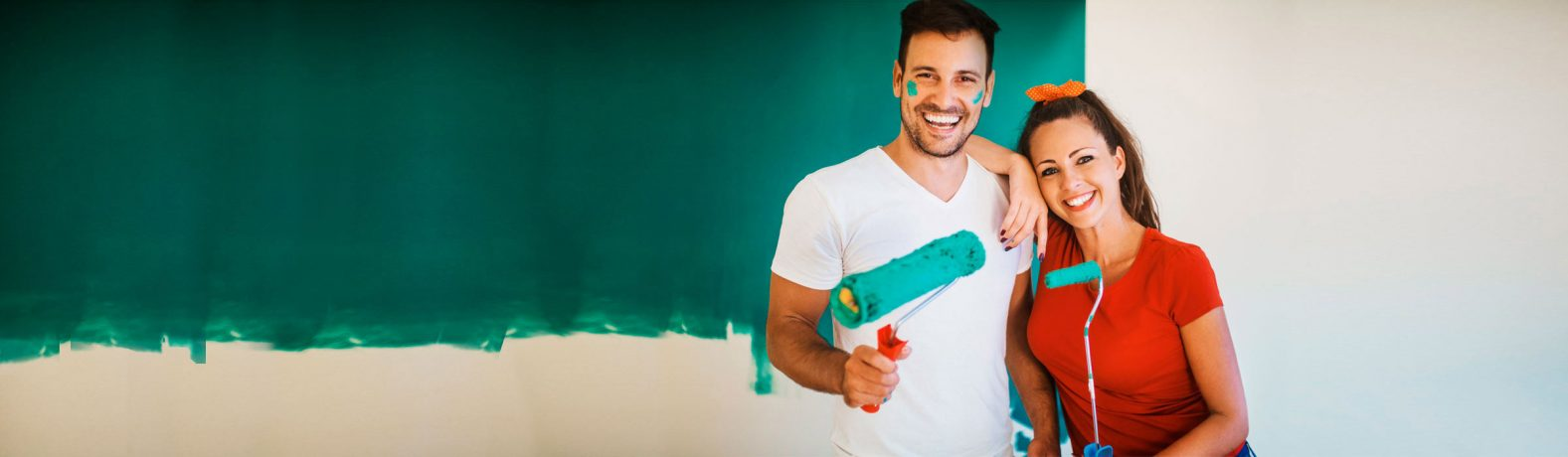 Junges Paar malt eine Wand