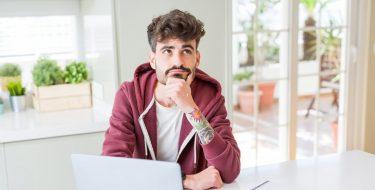 Junger Mann mit Bart schaut fragend