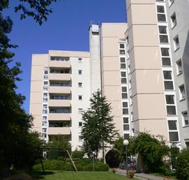 Mehrere Hochhäuser mit Bäumen und grüner Wiese davor.