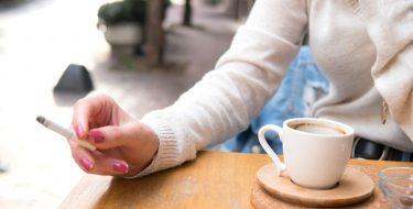 Frauenhand mit Zigarette zwischen den Finger