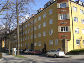 Gelbes Hochhaus mit parkenden Autos davor.