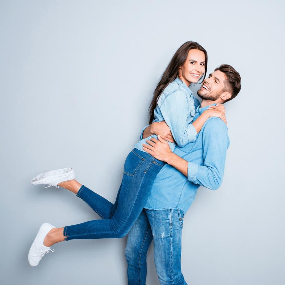 Junger Mann und junge Frau freuen und umarmen sich