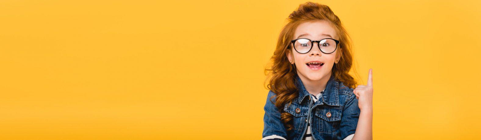 Mädchen mit Brille zeigt nach oben
