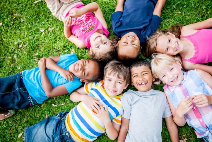 Kinder liegen auf einer Wiese