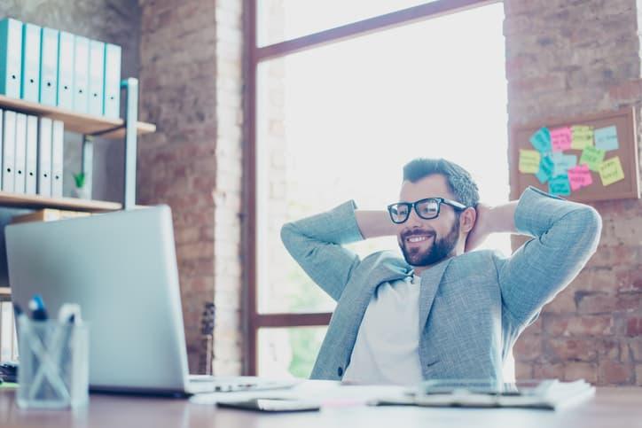 Junger Mann sitzt im Büro vor einem Bildschirm