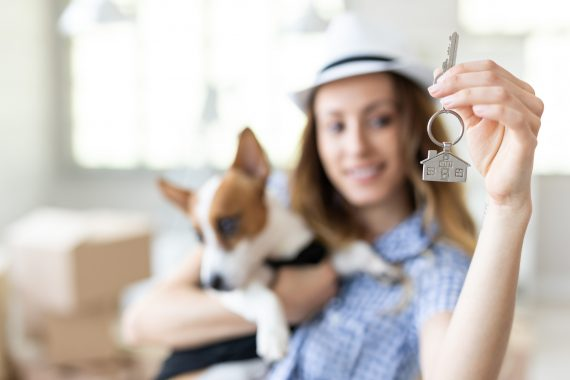Frau hält Schlüssel für Eigenheim hoch