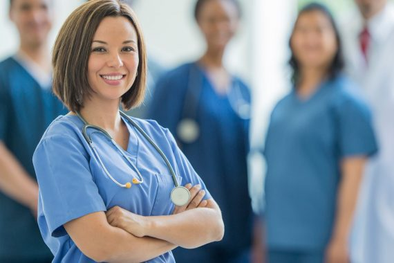 junge Ärztin lächelt in die Kamera