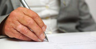 Alte Hand unterschreibt eine Patientenverfügung