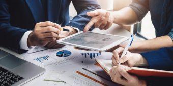 Drei Menschen schauen sich Aktienkurse an