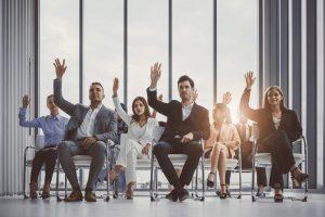 Geschäftsleute sitzen und heben die Hand