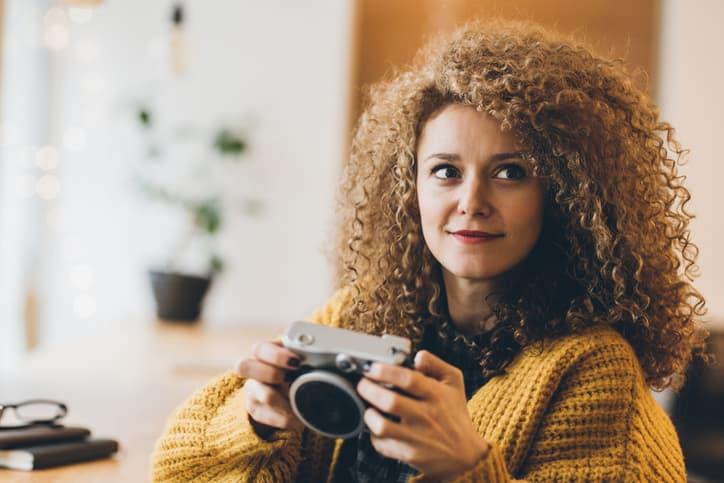 Schöne Lockige Frau mit Kamera