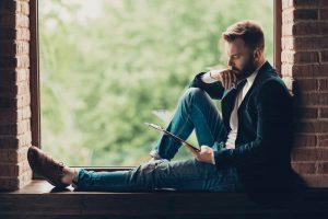 CEO in Jacke und Jeans, sitzt auf der Fensterbank