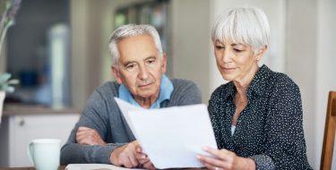 Älteres Ehepaar schaut in Unterlagen