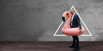 Mann im Anzug mit Flamingo Schwimmreifen
