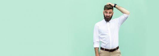 Junger Mann mit Bart kratzt sich am Kopf