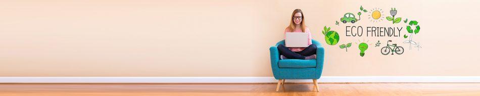 Junge Frau mit Brille sitzt auf einem Sessel mit Laptop