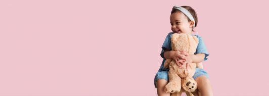 Kleines Mädchen sitzt auf einem Stuhl und hat einen Teddybär im Arm