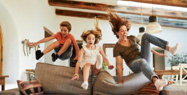 Mutter hüpft mit Kindern übers Sofa