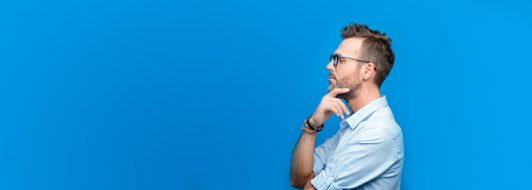 Mann mit Brille schaut zur Seite und hat Hand auf den Kinn