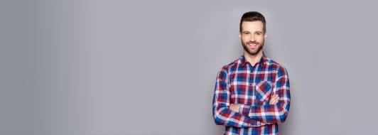 Junger Mann im Karierten Hemd mit verschränkten Armen
