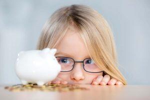 Mädchen mit Brille betrachtet Sparschwein auf dem Tisch
