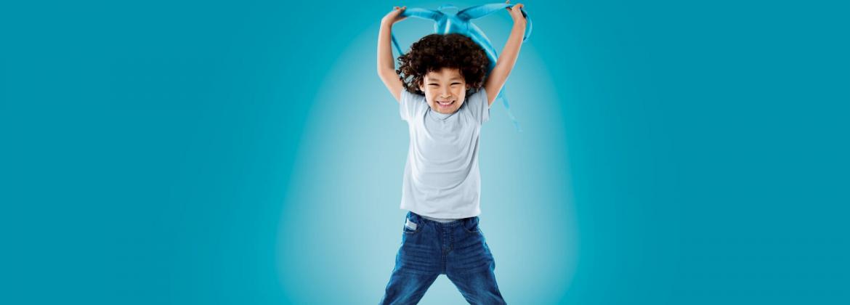 Junge freut sich und hebt Rucksack in die Höhe