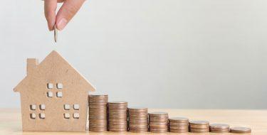 Stapel mit Münzen führt zu einem Sparhaus