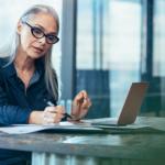 Ältere Arbeitnehmerin mit Brille am Laptop