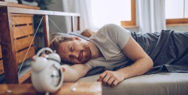 Ein Mann liegt schlaflos im Bett