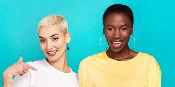 Zwei Freundinnen stehen nebeneinander und lächeln