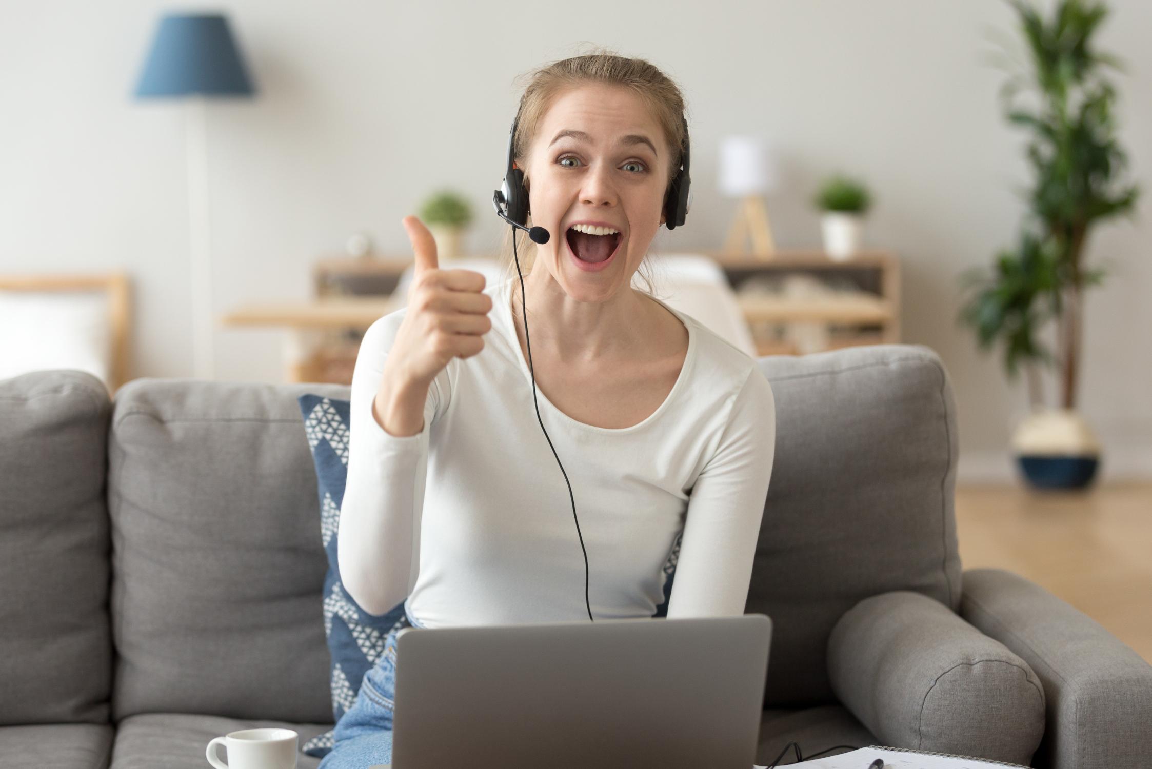 Frau sitzt auf einem Sofa mit Laptop und Headset
