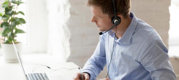 Mann arbeitet am Laptop mit Headset