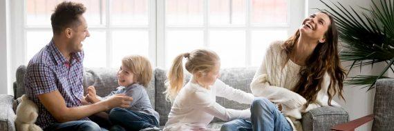 Frau und Mann spielen mit Kinder auf dem Sofa