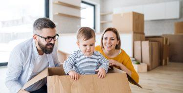 Vater und Mutter beobachten Kind im Karton