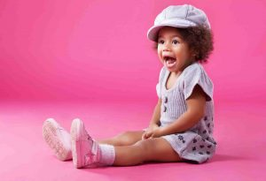 Mädchen sitzt auf den Boden und freut sich