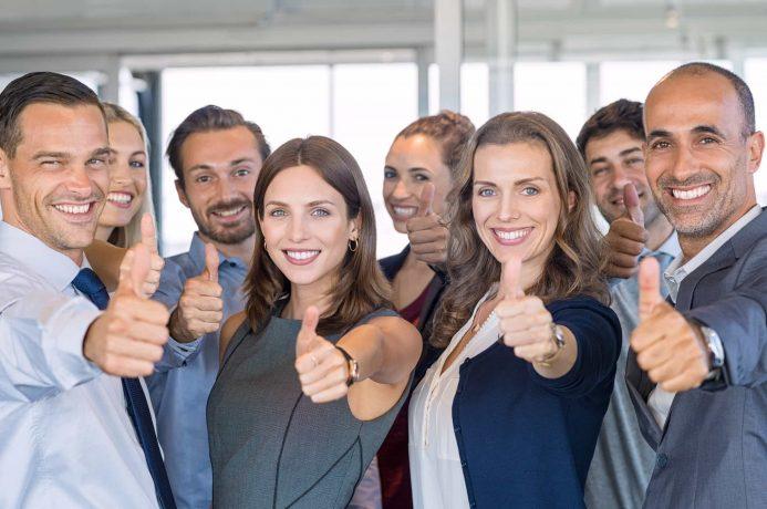 Acht Geschäftsleute zeigen die Daumen hoch