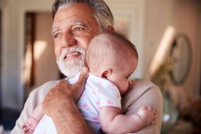Großvater hält Enkelkind im Arm
