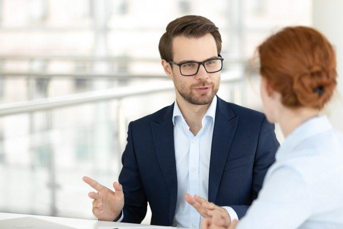Geschäftsmann berät eine junge Frau