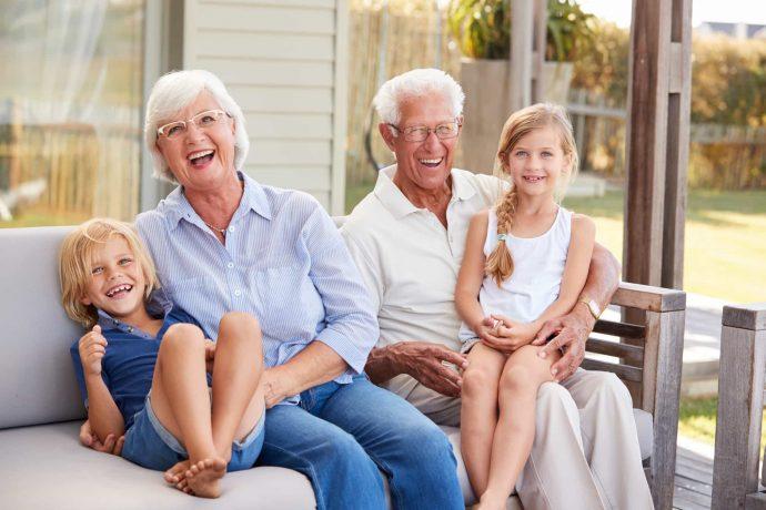 Großeltern mit Enkelkinder freuen sich und lachen